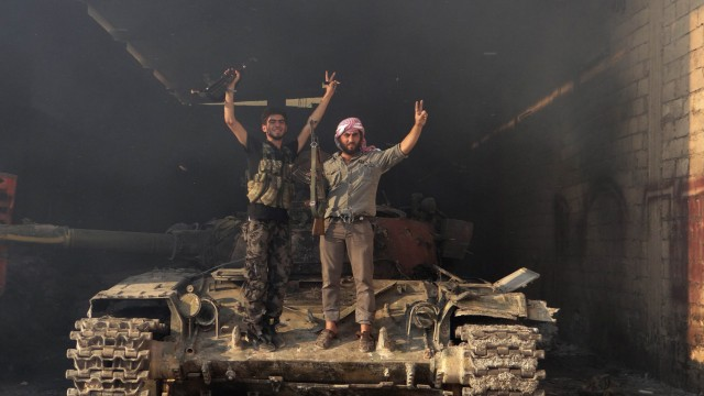 Two members of the Free Syrian Army stand on a tank as they gesture 'V' for victory in the Saraqib area near the northern city of Idlib