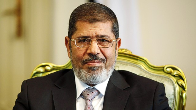 Egypt's President Mursi smiles during meeting with South Korea's presidential envoy and former Foreign Minister Yu at the presidential palace in Cairo