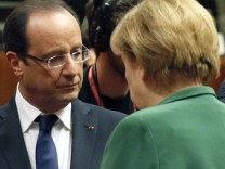 France's President Francois Hollande chats with Germany's Chancellor Angela Merkel at a European Union leaders summit in Brussels