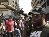A Lebanese Sunni Muslim gunman holds an RPG as he walks through the streets in Tripoli, as protests take place in city after the assassination of a senior intelligence official in Beirut