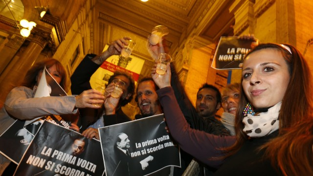 People hold pictures of Italy's former PM Berlusconi with words that read 'You Never Forget Your First Time', as they celebrate after Berlusconi was sentenced to jail for tax fraud in downtown Rome