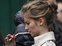 A student smokes in a street in Moscow