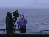 A reporter does a live broadcast at the New York Harbor as Hurricane Sandy approaches New York