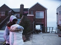 Deoadato and Denino hug in front of their aunt's house destroyed by rising waters from last night's storm surge due to Hurricane Sandy in New York
