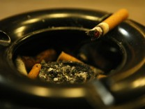 A cigarette lies in ashtray in front of a pub in Bensheim