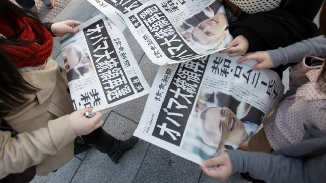 People read extra edition of newspapers reporting U.S. President Barack Obama's re-election in Tokyo