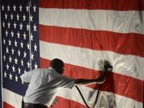 Hotel employee Denzil Telphia, of Boston, Mass., steams the wrinkles from an American flag hanging as a backdrop at Elizabeth Warren's election night party  in Boston