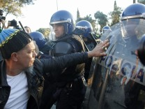 Protesters clash with police officers during a demonstration against German Chancellor Merkel in Lisbon