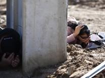 Israelis take cover as a siren sounds warning of incoming rockets in Kiryat Malachi