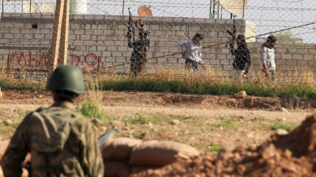 Free Syrian Army fighters hold up their weapons in the Syrian town of Ras al-Ain, with a Turkish soldier standing guard in the Turkish border town of Ceylanpinar