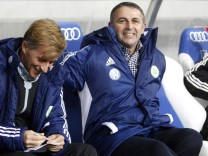 Vfl Wolfsburg's manager Allofs sits on the bench next to co-coach Jonker ahead of their German first division Bundesliga soccer match against Hoffenheim in Sinsheim