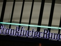 The logo of German newspaper Frankfurter Rundschau is lit at its headquarters in Frankfurt