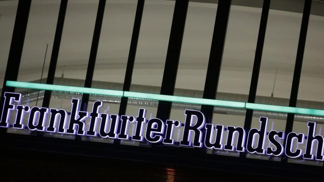 The logo of German newspaper Frankfurter Rundschau is lit at its headquarters in Frankfurt