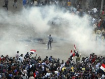 Protesters run from tear gas released by riot police during clashes at Tahrir square in Cairo