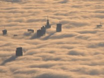 Tops of high rise buildings stick out from a blanket of think fog covering Warsaw