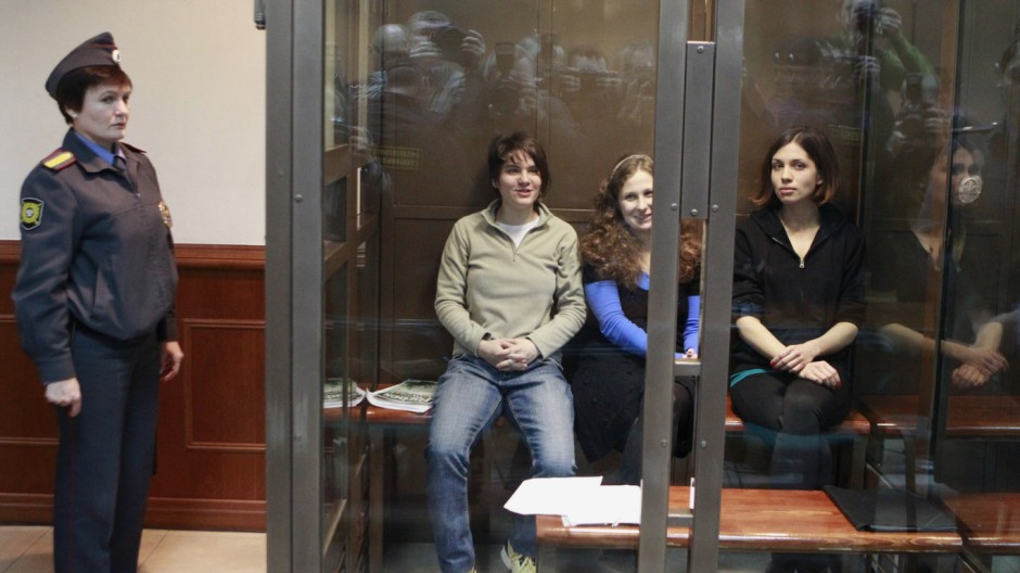 Members of the female punk band 'Pussy Riot' sit in a glass-walled cage before a court hearing in Moscow