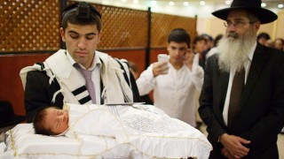 File photo of Jewish man holding his baby son before his circumcision in Jerusalem