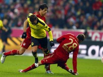 Badstuber of Bayern Munich twists his knee as he challenges Goetze of Borusia Dortmund during their German Bundesliga soccer match in Munich