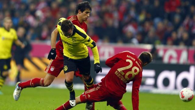 Badstuber of Bayern Munich twists his knee as he challenges Goetze of Borusia Dortmund during their German Bundesliga soccer match in Munich