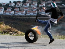 Palestinian demonstrator kicks burning tyre towards Israeli security officers during clashes in the West Bank village of Nabi Saleh