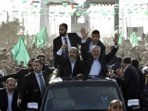 Hamas chief Meshaal, riding in a car with senior Hamas leader Haniyeh, gestures to the crowd upon his arrival in Gaza City