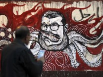 A man take a picture of a mural of Egypt's President Mohamed Mursi and with Arabic words that reads 'Leave' on the wall of the presidential palace in Cairo