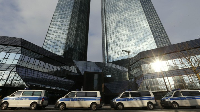 Police vehicles are parked outside the headquarters of  Deutsche Bank AG in Frankfurt