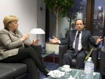 German Chancellor Merkel speaks with French President Hollande during a meeting on the sidelines of an EU summit in Brussels