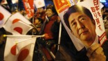 A voter holds an election campaign leaflet of Japan's main opposition Liberal Democratic Party's leader Abe in Tokyo
