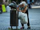 Eine Frau sucht in Mülleimern der thüringischen Stadt Weimar nach Pfandflaschen.