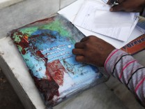 A rescue worker checks blood-stained forms which belong to Nasima Bibi, a female worker of an anti-polio drive campaign who was shot by gunmen, in Karachi
