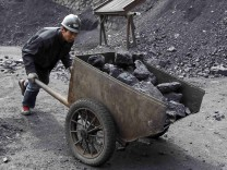 A worker pushes a cart at a coal mine owned by Puda Coal Inc. in Pinglu