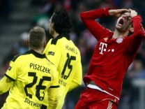 Bayern Munich's Mueller reacts next to Borussia Dortmund's Piszczek and Hummels during German first division Bundesliga soccer match in Munich