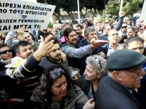 Angry demonstrators protest as lawmakers discuss new austerity laws in Cyprus' parliament