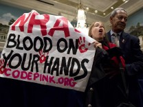 A protestor holding up a sign is removed by a security guard during a speech by Wayne LaPierre Executive Vice President of the National Rifle Association (NRA  during a press conference in Washington