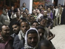 Men queue outside a polling station to vote during the final stage of a referendum on Egypt's new constitution in Bani Sweif