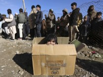An internally displaced Afghan girl sits inside a box as she waits for the distribution of winter assistance in Kabul