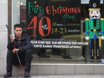 A blind beggar asks for alms outside a Christmas decorated shop i