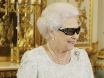 Britain's Queen Elizabeth watches a preview of her Christmas message with a pair of 3D glasses in London