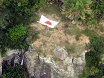 Aerial photo from Kyodo News shows Japan's national flag on one of a group of disputed islands known as Senkaku in Japan and Diaoyu in China, in the East China Sea