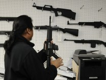 Aristotle Rogel of Aegis Trading Enterprises gun shop handles a Umarex Colt M4 semi automatic rifle in Burbank California