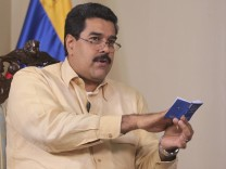 Venezuela's Vice President Nicolas Maduro speaks while holding a copy of his country's constitution during an interview in Caracas