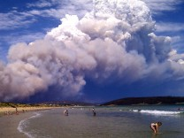 Smoke from a bushfire billows over beach goers at Carlton, east of Hobart