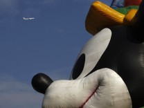 A plane flies past a musical parade at Hong Kong Disneyland