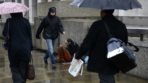 A homeless man sits in the rain as commuters make their way to work across London Bridge in London