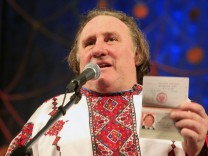 French film star Gerard Depardieu, wearing a local costume, shows his passport during a ceremony in the town of Saransk