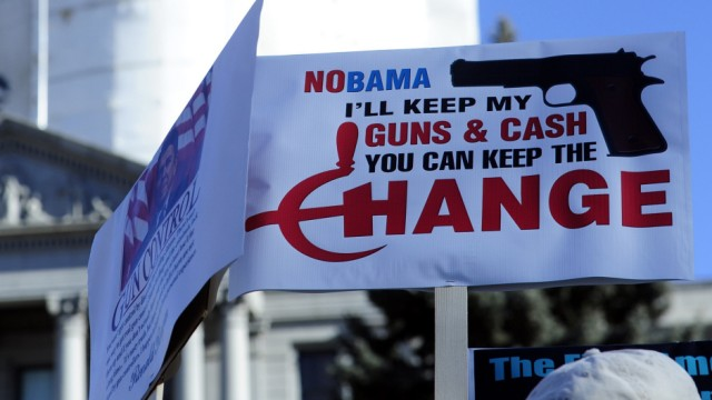 Anti-gun legislation activists hold signs at the Colorado State Capital Building during an anti-gun control legislation rally organized by Guns for Everyone in Denver, Colorado