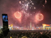 North Koreans take pictures with their mobile phones as they watch fireworks to bring in the new year in Pyongyang
