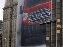 Workers hang a Ford Motor banner on the side of a building across from Cobo Center in advance of media preview of North American International Auto show in Detroit
