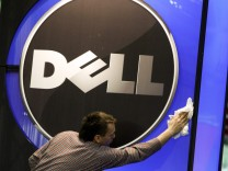 File of a man wiping logo of Dell IT firm at CeBIT exhibition centre in Hannover